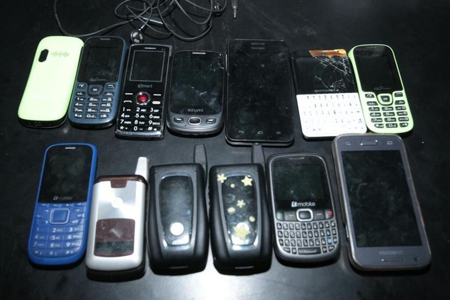 13 teléfonos celulares fueron decomisados al grupo. (Foto Prensa Libre: Paulo Raquec)