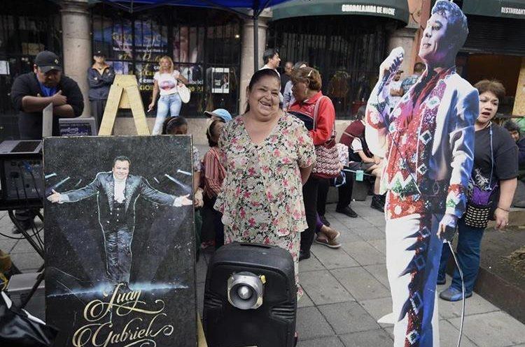 Una aficionada posa junto a una figura tamaño real de Juan Gabriel (AFP).