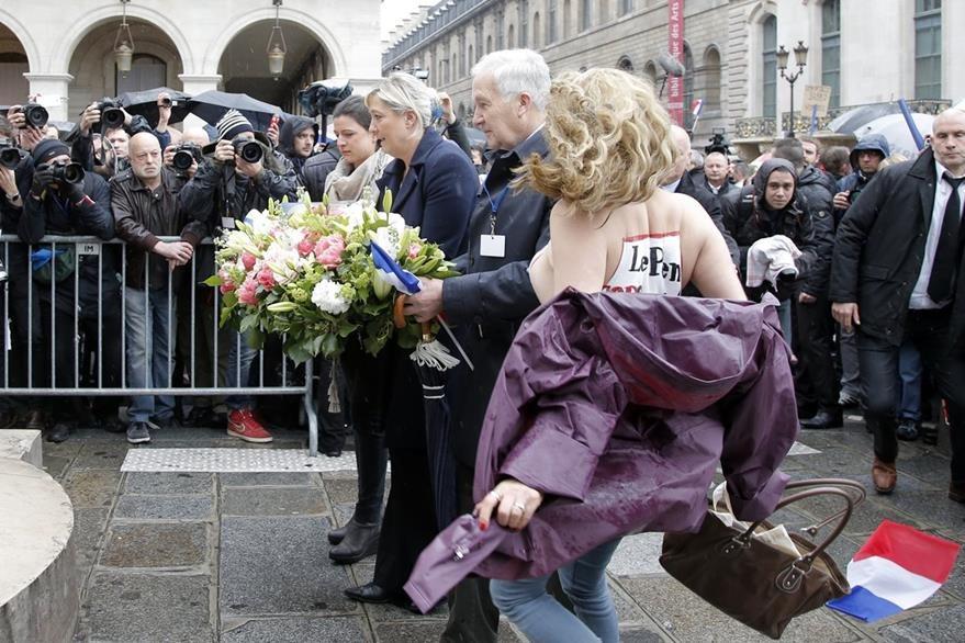 El momento en que las activistas irrumpieron en el acto de Le Pen cuando colocaba una ofrenda floral en el monumento al trabajo. (Foto Prensa Libre: AP).