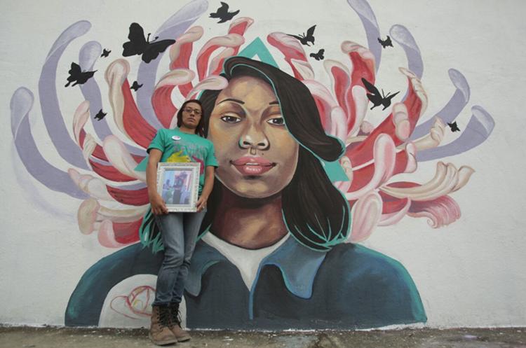 El rostro de Ashley Gabriela Méndez, quien falleció durante el incendio en el Hogar Seguro, fue pintado en uno de los murales, sobre el cual está recostada la madre, Dacia Ramírez. (Foto Prensa Libre: Carlos  Hernández)