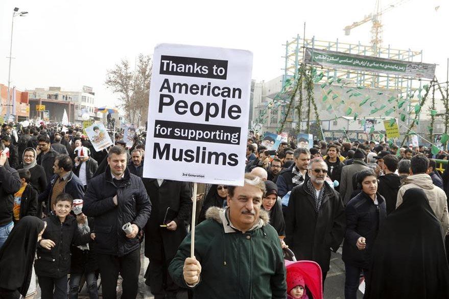 """Un iraní muestra un mensaje """"Gracias al pueblo americano por apoyar a los musulmanes"""". (EFE)."""