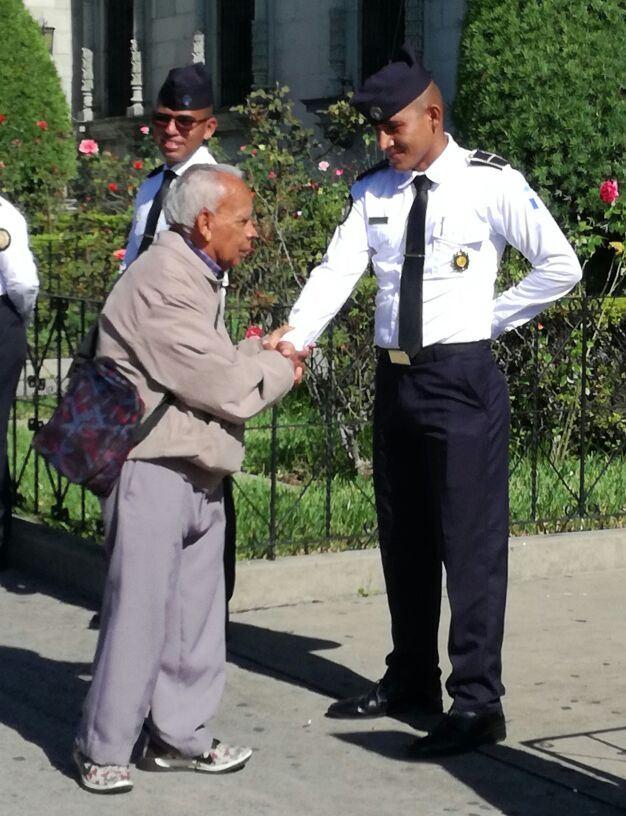 Un ciudadano saluda a los agentes de la PNC que resguardan el Palacio Nacional. (Foto Prensa Libre: PNC)