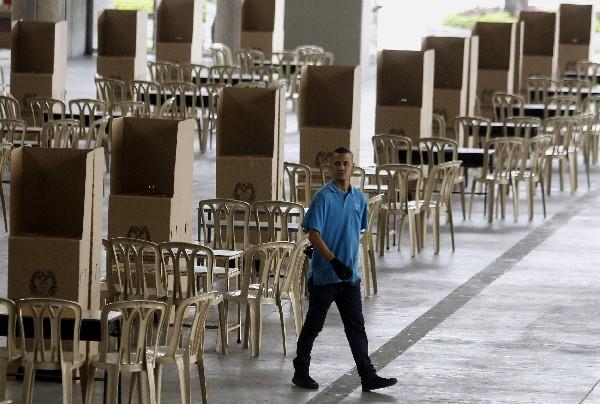 Un colombiano prepara puestos de votación para el plebiscito. (Foto Prensa Libre:EFE).