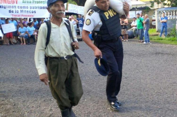 Un agente de la PNC brinda ayuda a una persona de la tercera edad durante la manifestación pacífica.