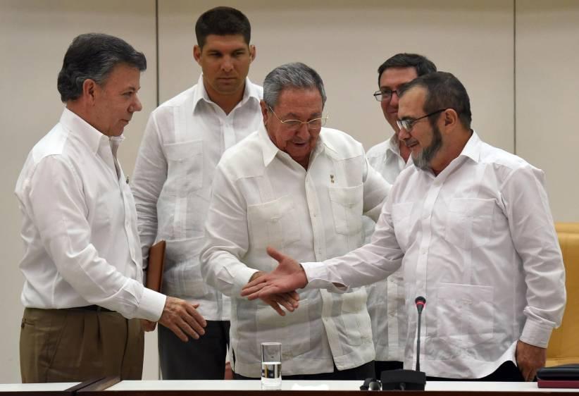 "El presidente Juan Manuel Santos (izquierda), saluda al jefe de las Farc Rodrigo Echeverri ""Timochenko"", se saludan en La Habana, observa el presidente Raúl Castro. (Foto: Hemeroteca PL)."
