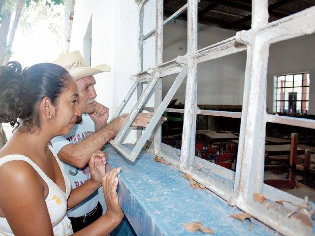 Padres de familia observan las condiciones en las que se encuentran las ventanas y paredes de los salones de clases. (Foto Prensa Libre: Héctor Contreras).