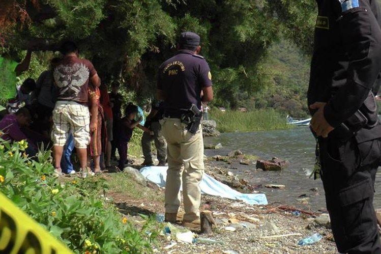 Autoridades colocán el cadáver de Castro a la orilla del lago cubierto con una manta. (Foto Prensa Libre: Ángel Julajuj)