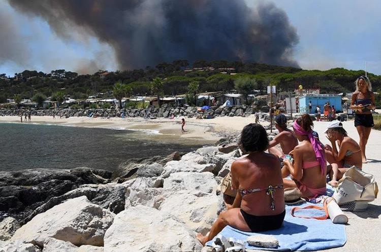 Turistas observan el incendio en Bormes-les-Mimosas, sureste de Francia. (AFP).