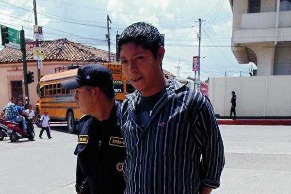Gilbert Neftalí Godoy López es trasladado al Tribunal de Sentencia de Jalapa por un agente de la Policía Nacional Civil. (Foto Prensa Libre: Hugo Oliva)