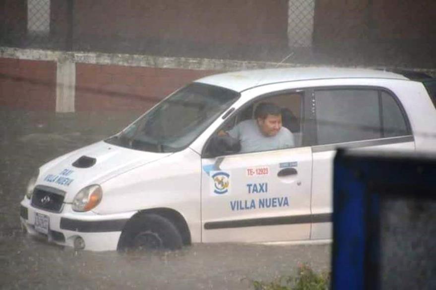 Un taxista intenta salir de la inundación en la calzada Aguilar Batres. (Foto Prensa Libre: Conred)