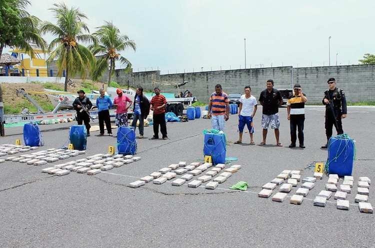 Ocho de los nueve capturados  junto a parte de los paquetes de cocaína  incautados en Escuntla.