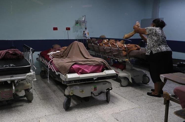 Familiares y personas que se encuentran en el lugar ayudan a los enfermos mientras llega a atenderlos alguien del hospital.