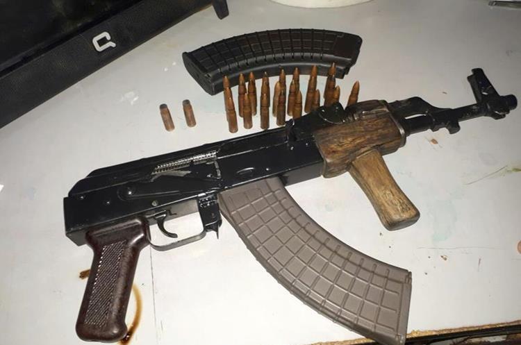 El fusil Ak-47 y las municipios que le fueron decomisados a los capturados. (Foto Prensa Libre: Mike Castillo)