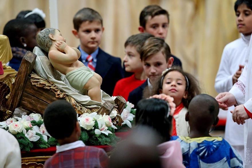 Niños rodean una imagen del Niño Jesús durante la misa de Navidad dirigida por el Papa. (EFe)
