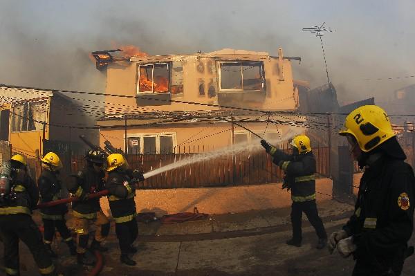 Bomberos combaten las llamas en Playa Ancha en la ciudad de Valparaíso. (Foto Prensa Libre: EFE).