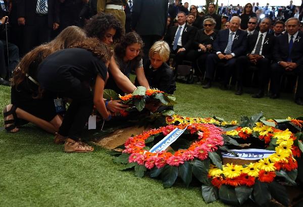 Nietos de Shimon Peres, depositan una corona de flores sobre su tumba.(Foto prensa Libre:EFE).