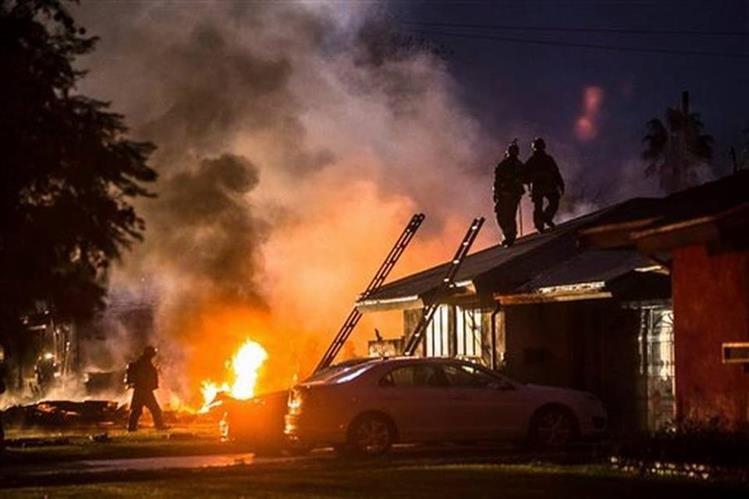 Una columna de humo y fuego marca el lugar en el que un pequeño avión se estrelló sobre dos viviendas en Riverside, en el sur de California. (Foto Prensa Libre: AFP)
