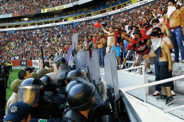 Los barra brava del Atlas protagonizaron actos bandálicos en el duelo de vuelta de los cuartos de final de la Liga MX. (Foto Prensa Libre: EFE)
