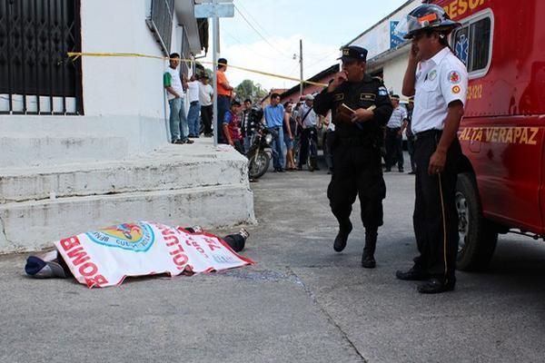 <p>Un bombero y un policía en la escena en donde mataron al desconocido en Cobán. (Foto Prensa Libre: Eduardo Sam)<br></p>