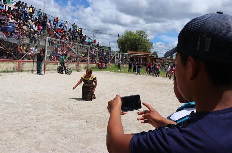 Uno de los curiosos graba con su teléfono celular el castigo al que fue sometida Tomasa Tzoc Tipaz, en San Antonio Ilotenango. (Foto Prensa Libre: Héctor Cordero).