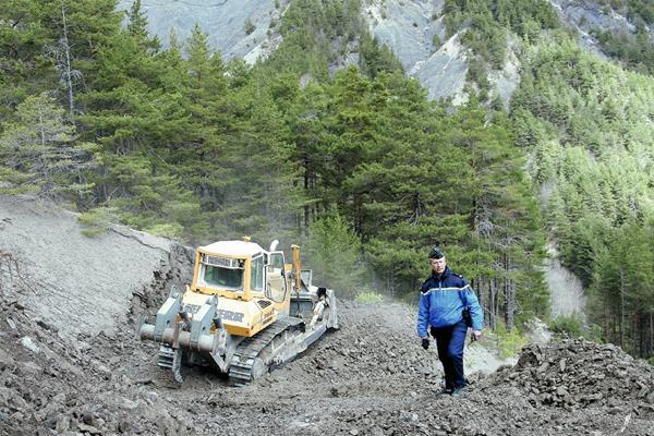 Un tractor abre camino al lugar donde se estrelló el avión de Germanwings en Seyne-les-Alps,Francia. (Foto Prensa Libre:EFE).
