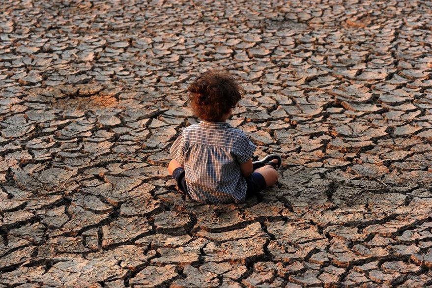 Un niño en medio de un río seco en Tegucigalpa, Honduras. (Foto Prensa Libre: AFP).