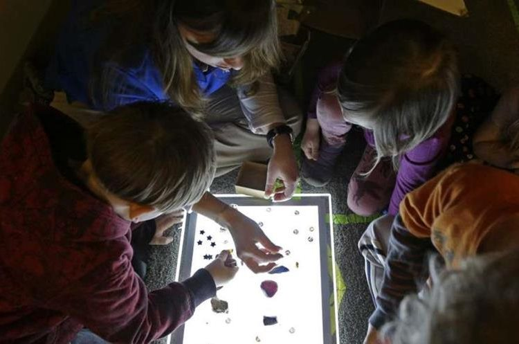 Amy Band, muestra varios objetos en una caja de luz a los niños en su aula del Verner Center en Asheville, Carolina del Norte. Foto Prensa Libre: AP.