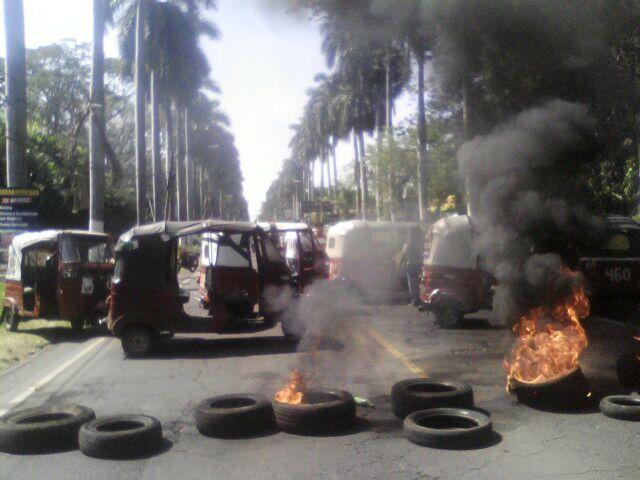 Pilotos de mototaxis queman neumáticos e impiden el paso de vehículos en la cabecera de Retalhuleu. (Foto Prensa Libre: Jorge Tizol)