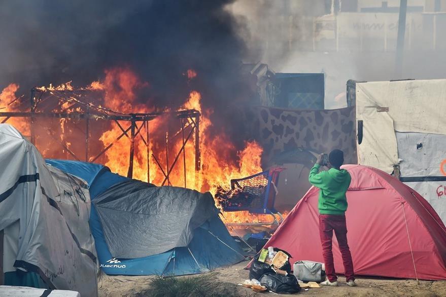 """Un hombre graba cómo su vivienda arde, durante el último día de desalojo de """"la jungla"""" del Calais. (Foto Prensa Libre: AFP)."""
