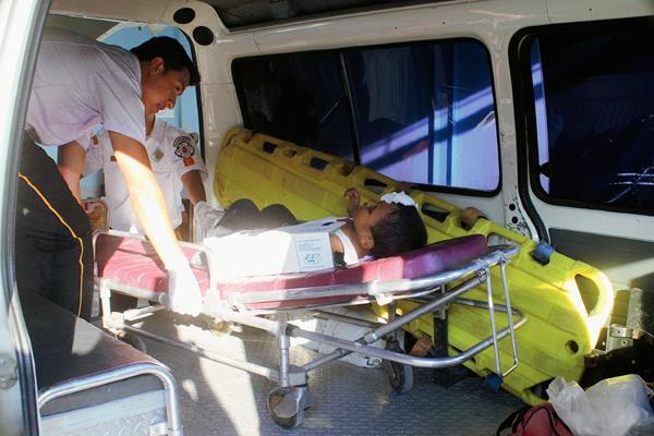 Un socorrista  examina  al niño que cayó desde la ventana de un autobús en Jalapa, cuando regresaba de una actividad política en la capital. (Foto Prensa Libre: Hugo Oliva)