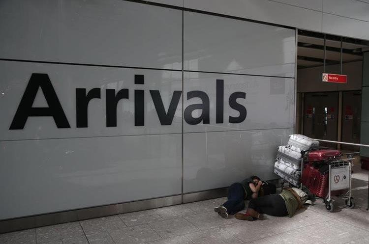 Varios pasajeros en el aeropuerto de Londres tuvieron que dormir en el suelo. (Foto Prensa Libre: AFP)