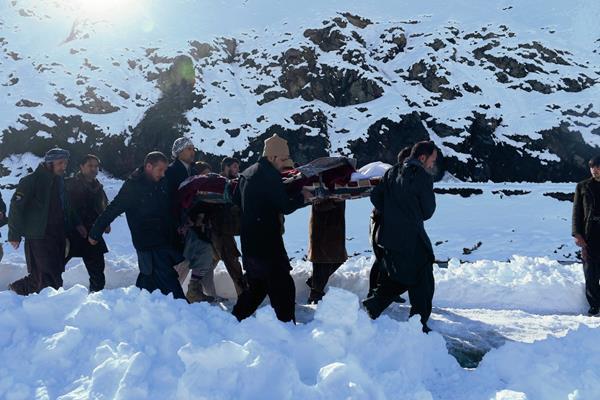 Afganos llevan el cuerpo de una víctima de las avalanchas en el distrito de Panjshir, al norte de Kabun. Más de 200 han muerto en los últimos días a causa de la naturaleza