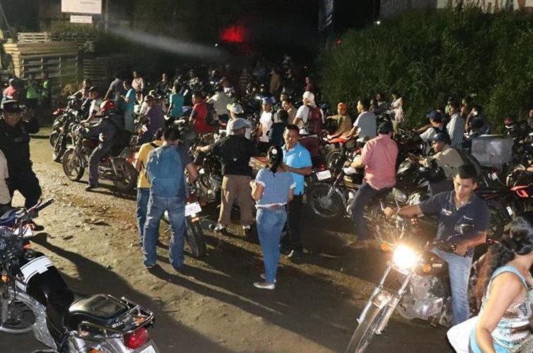 Trabajadores y vecinos observan el camión que volcó en el km 166 de la ruta al Succidente. (Foto Prensa Libre: Cristian Soto)