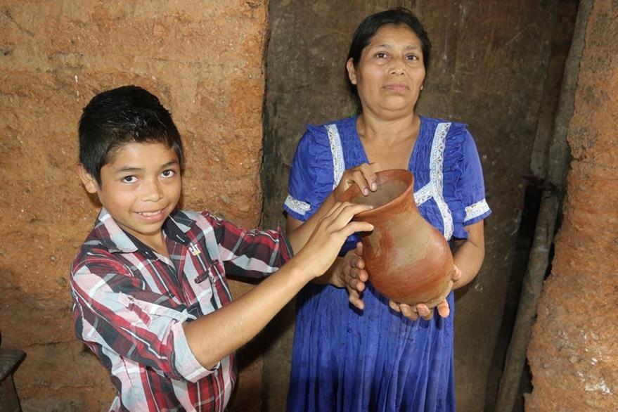 El menor y su mamá muestran uno de los artículos de barro que venden en la ciudad de Chiquimula. (Foto Prensa Libre: Edwin Paxtor).