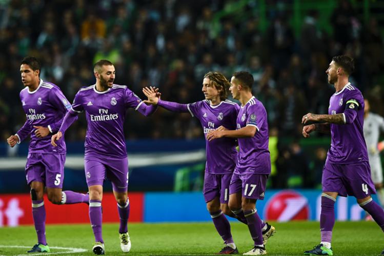 Benzema es felicitado por sus compañeros del Real Madrid por el gol del triunfo en Lisboa. (Foto Prensa Libre: AFP)