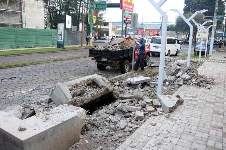 Un trabajador recoge los restos de las bancas y mesas que fueron demolidas de la vía pública, en la zona 3 de Xela. (Foto Prensa Libre: Carlos Ventura)