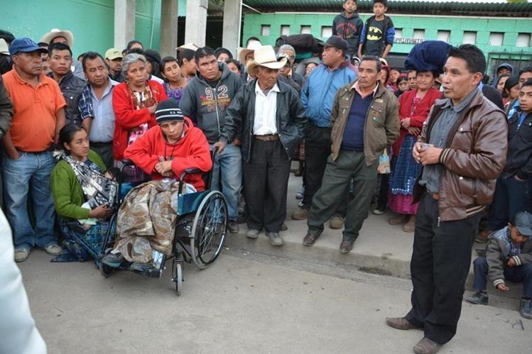 Gregorio Can Ortiz, -en silla de ruedas- habría sido estafado por los dos individuos de chumpa café a la derecha. (Foto Prensa Libre: Édgar Sáenz).