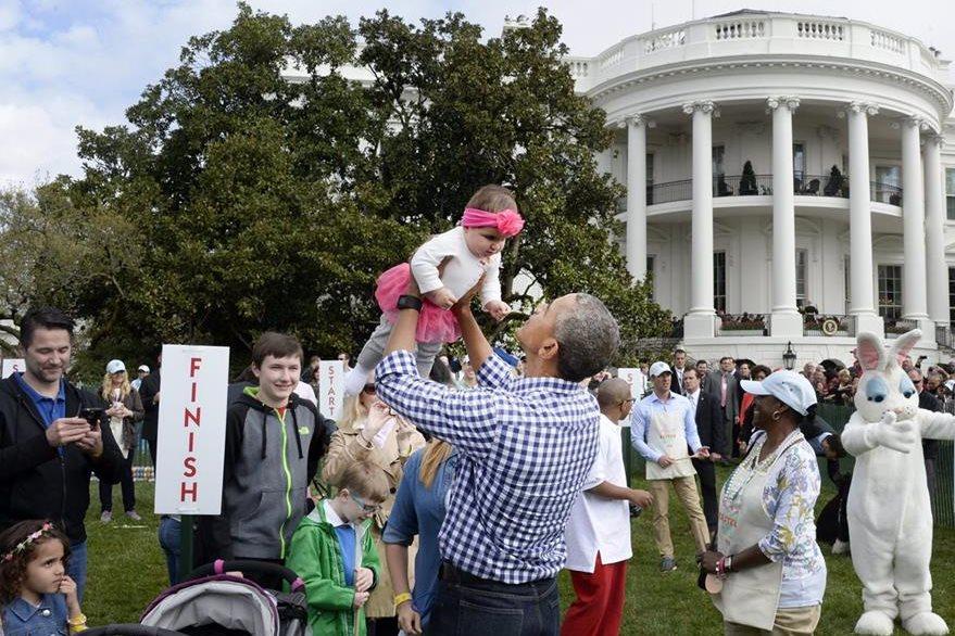 El presidente de EE. UU., Barack Obama sostiene a una niña en el jardín Sur de la Casa Blanca en Washington. (Foto Prensa Libre: EFE).
