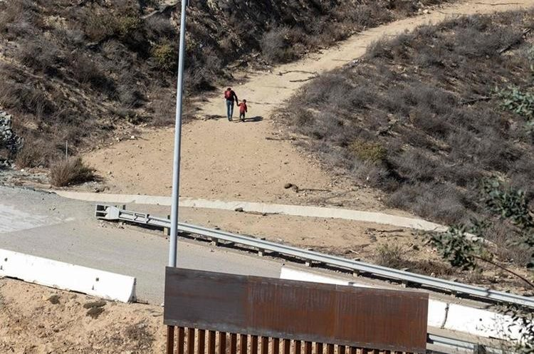 FOTO 2: El hombre y su hijo parecen retornar para buscar otro camino. (Foto Prensa Libre: AFP)