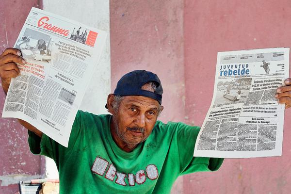 Un vendedor muestra los diarios oficiales en una calle de La Habana, Cuba. (Foto Prensa Libre: EFE).