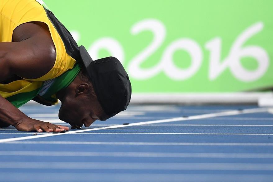 Bolt besa la pista luego de ganar el triple triplete el viernes en Río. (Foto Prensa Libre: EFE)