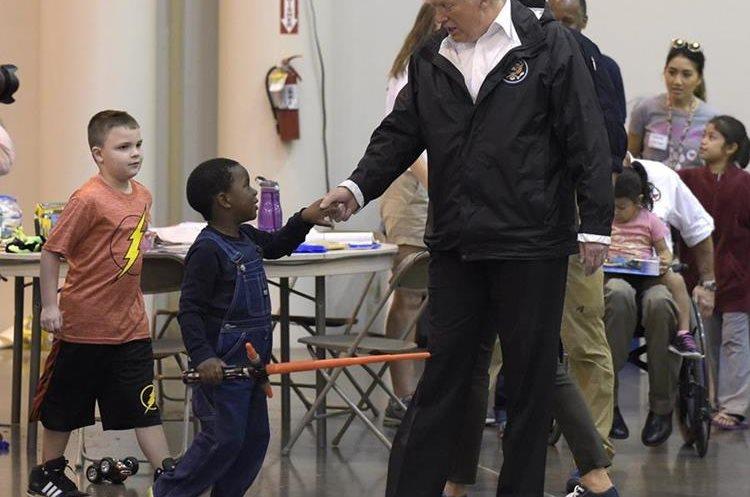 Donald Trump da la mano a un niño víctima del paso del Huracán Harvey en un refugio de Texas.