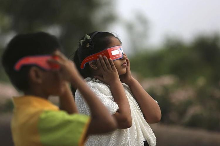 Indian children watch a partial solar eclipse in Hyderabad, India, Wednesday, March 9, 2016 Indian people in northeast and eastern coastal strip of the sub-continent viewed a partial solar eclipse as a total eclipse of the sun unfolded over Indonesia on Wednesday, briefly plunging cities into darkness and startling wildlife. (AP Photo /Mahesh Kumar A.)