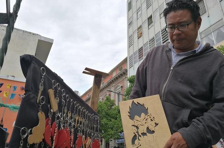 Cristian Santos hace rostros en madera y los vende en la Sexta Avenida de la zona 1 de la capital. (Foto Prensa Libre: César Pérez)