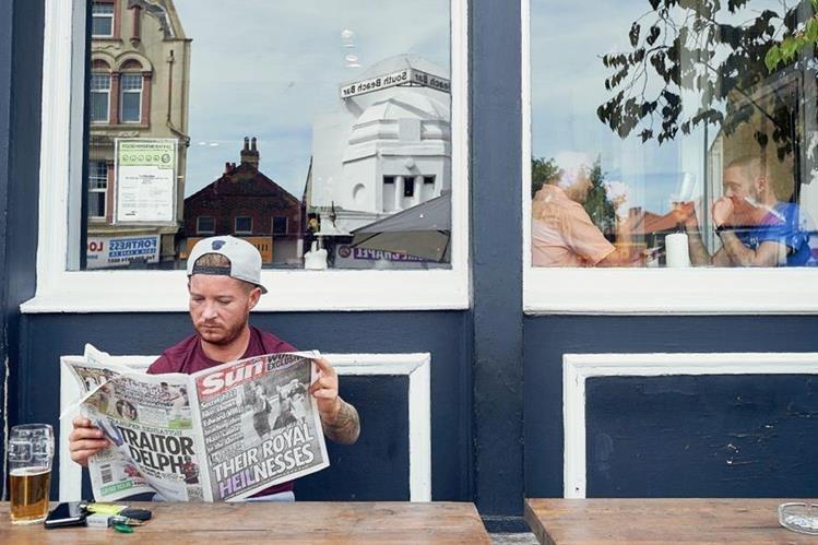 Un británico lee un ejemplar del periódico  The Sun que muestra en su portada una foto de la reina Isabel II haciendo el saludo nazi.(Foto Prensa Libre: AFP).
