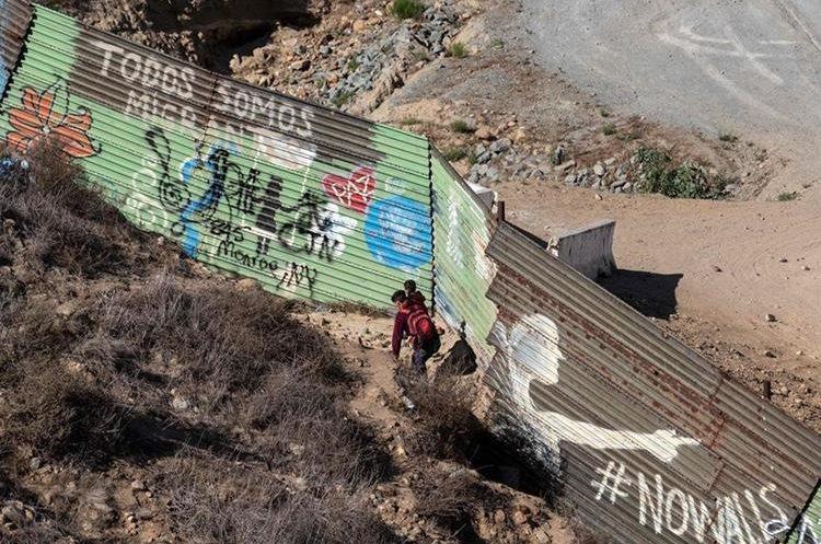 FOTO 3: Parecen intentar cruzar una valla. (Foto Prensa Libre: AFP)