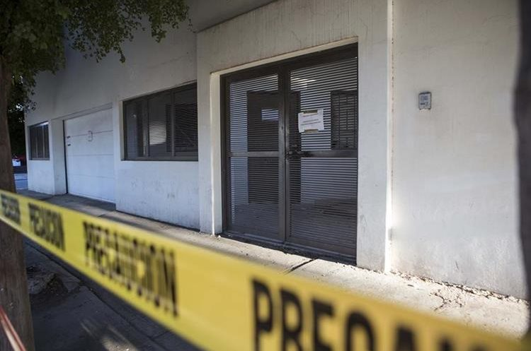 """Police tape surrounds the entrance of the home where marines engaged in a gun battle during the search for Mexican drug lord Joaquin """"El Chapo"""" Guzman, in Los Mochis, Mexico, Sunday, Jan. 10, 2016. Guzman apparently fled from the home Friday before authorities eventually caught him. A month or two of intensive renovations transformed the house into an architecturally unremarkable but completely enclosed structure. Windows and glass doors with horizontal grating were installed and the new walls that advanced right to the sidewalk. (AP Photo/Christian Palma)"""