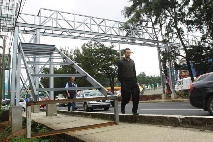 Vecinos que transitan por el kilómetro 14.5, calzada Roosevelt, son afectados por la construcción de pasarela que cubre la banqueta. (Foto Prensa Libre: Álvaro Interiano)