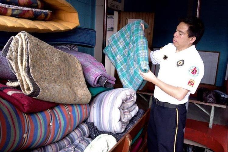 Un socorrista ordena colchas que son utilizadas en el albergue habilitado en la cabecera de San Marcos. (Foto Prensa Libre: Genner Guzmán)
