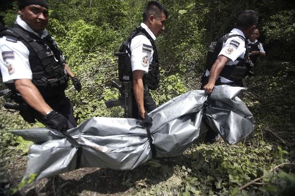 Agentes traladan a uno de los tres cadáveres encontrados en una fosa. (Foto Prensa Libre:AFP).